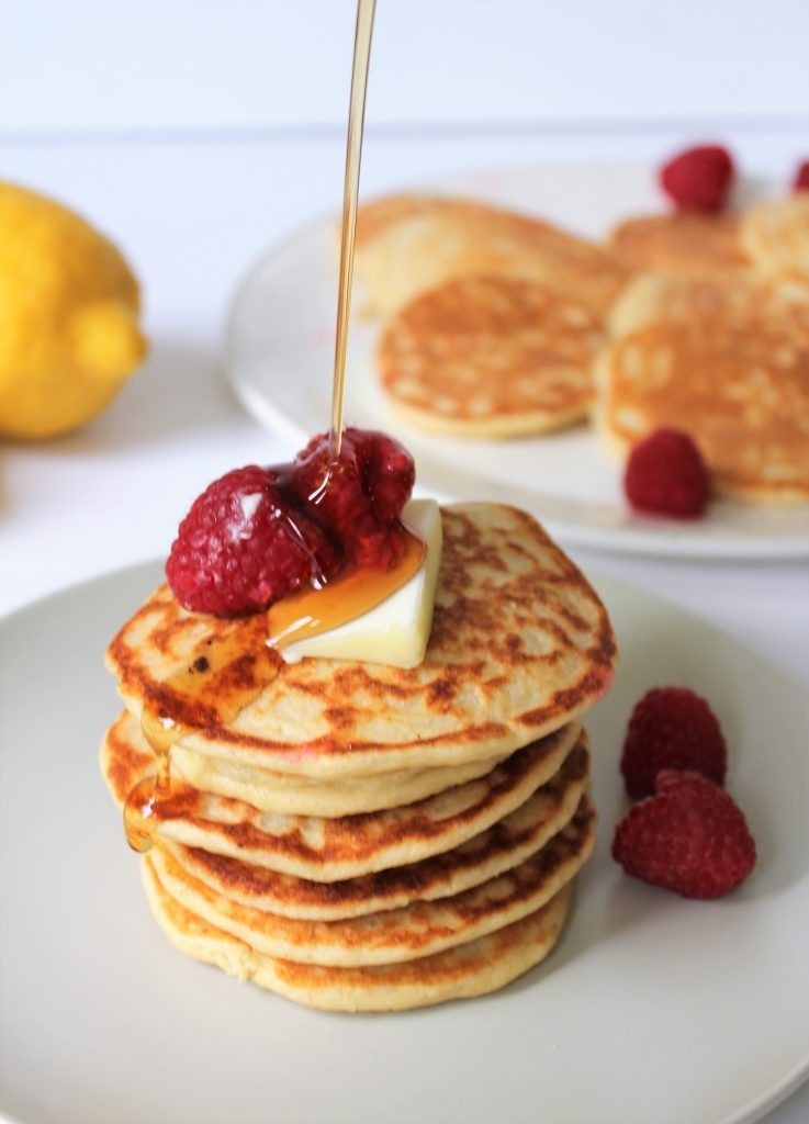 Healthy Lemon Ricotta Pancakes made with oat flour, naturally gluten free and refined sugar free. Topped with some raspberries and butter!