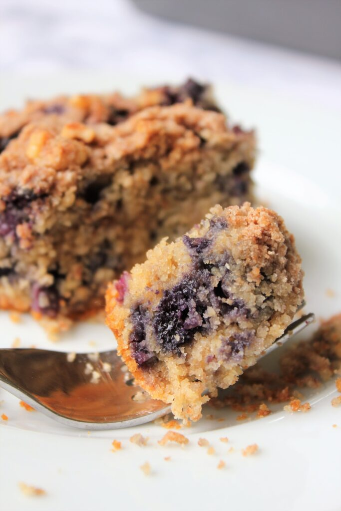 close up bite shot of a slice of healthy blueberry coffee cake