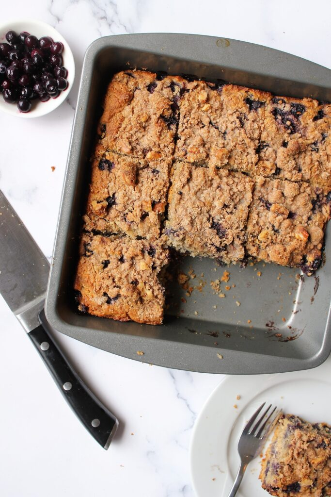Overhead shot of blueberry buckle, cut into slices with a couple missing