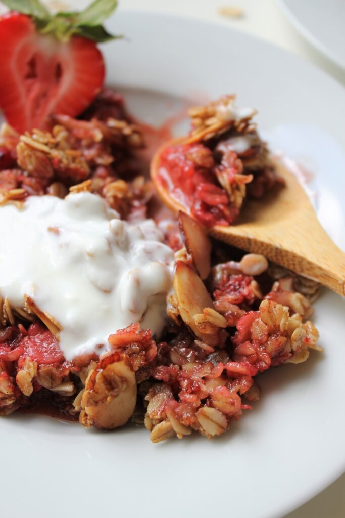 close up of a slice of strawberry crisp with a dollop of greek ypgurt on top