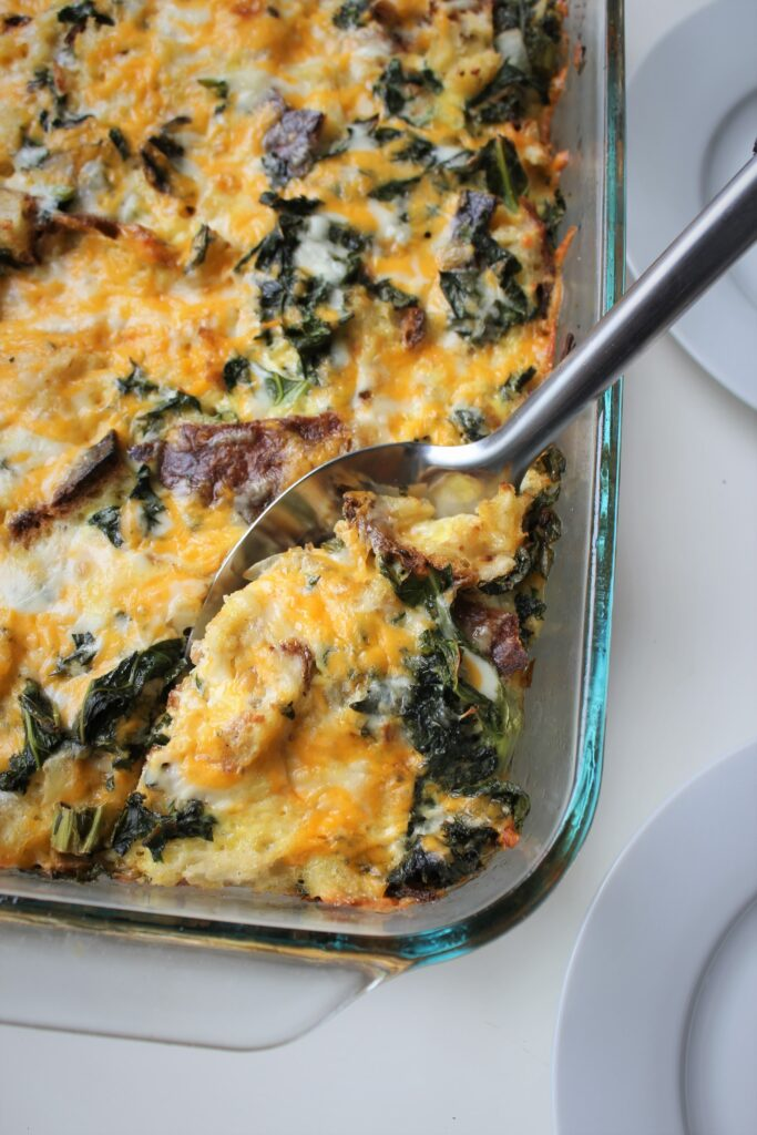 serving spoon serving the first portion of cheesy kale strata