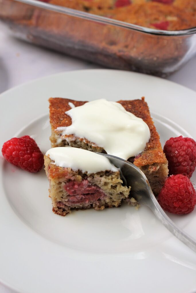 a slice of gluten free raspberry cake topped with more yogurt