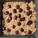 Close up of baking dish after baking vegan banana bread oat with melted chocolate chips on top