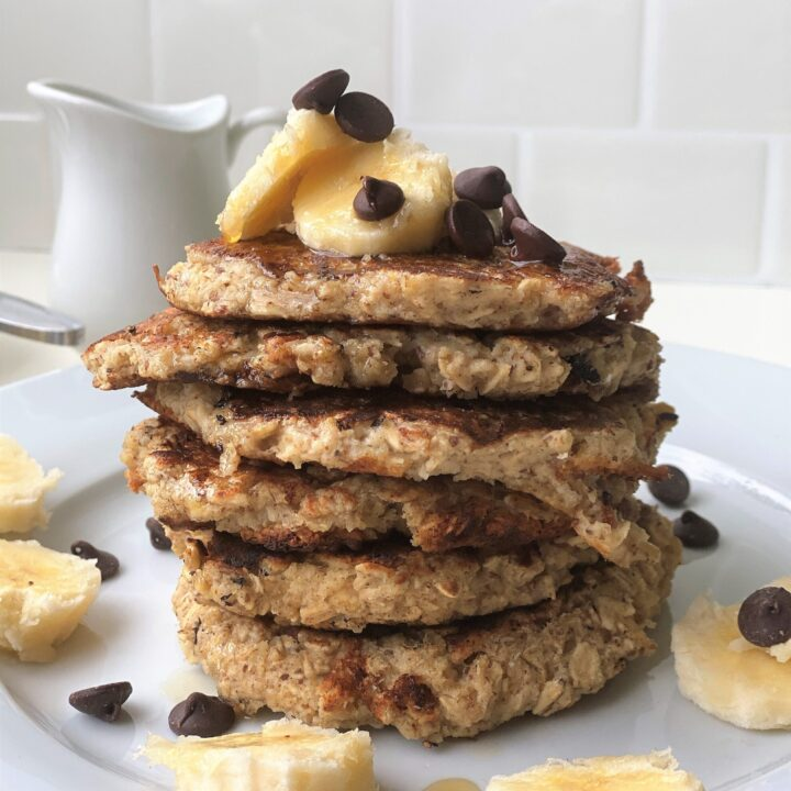 Stack of 6 vegan banana pancakes on a plate with a white backsplash in the background