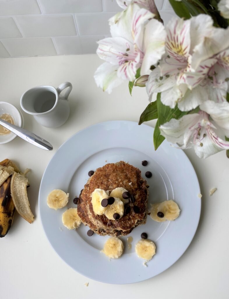 Bird eye view shot of stacked banana pancakes, with flowers and small milk jar
